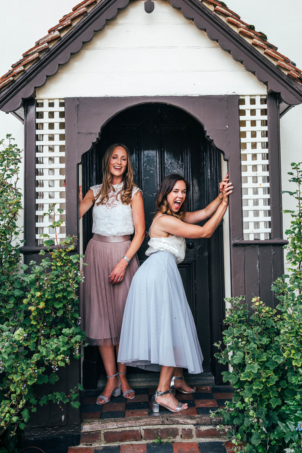 Laughing wedding guests in doorway for DIY Boho wedding. Essex Documentary Wedding Photographer