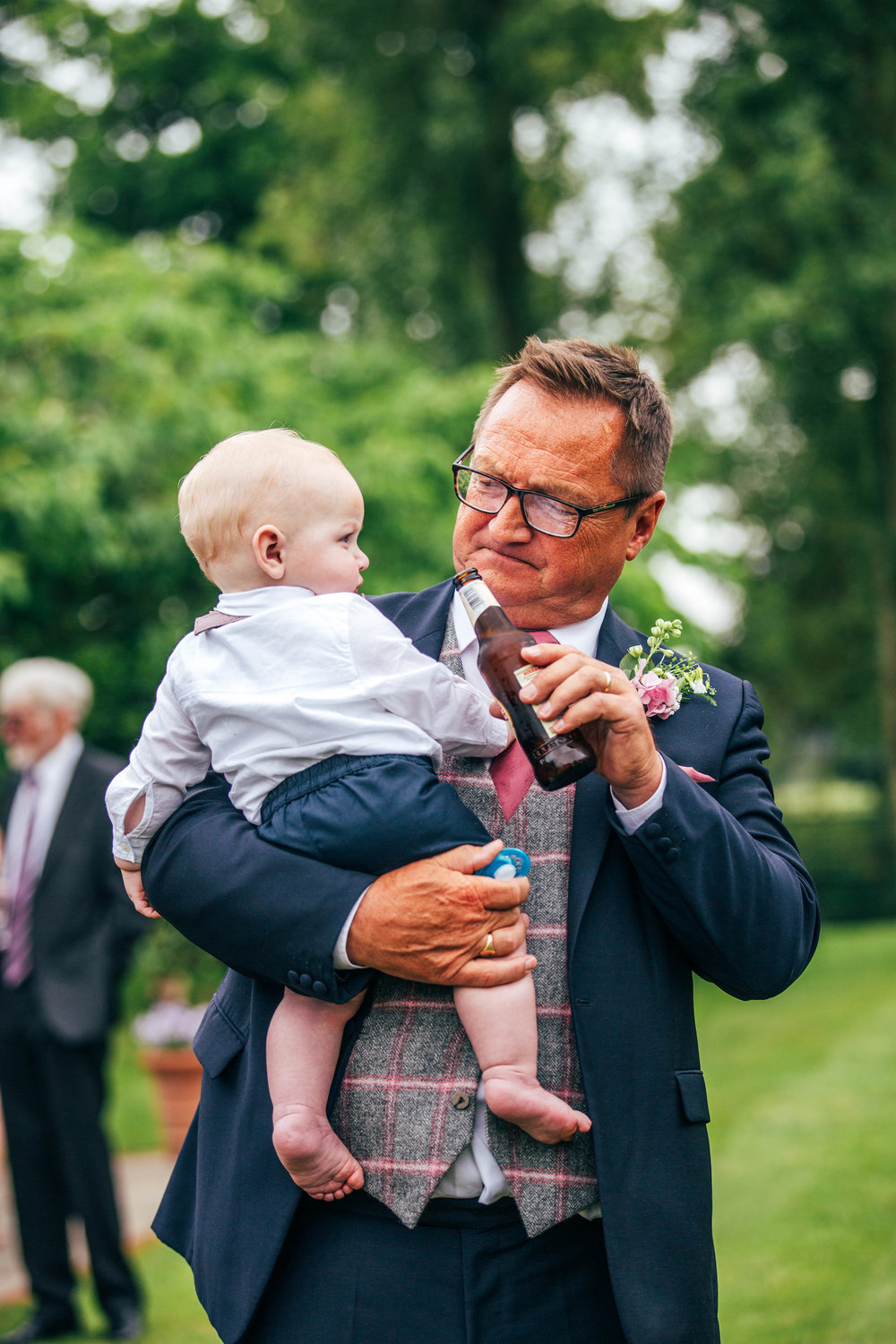 Wedding guest shows baby a beer at Blake Hall, Ongar.  Essex Documentary Wedding Photographer