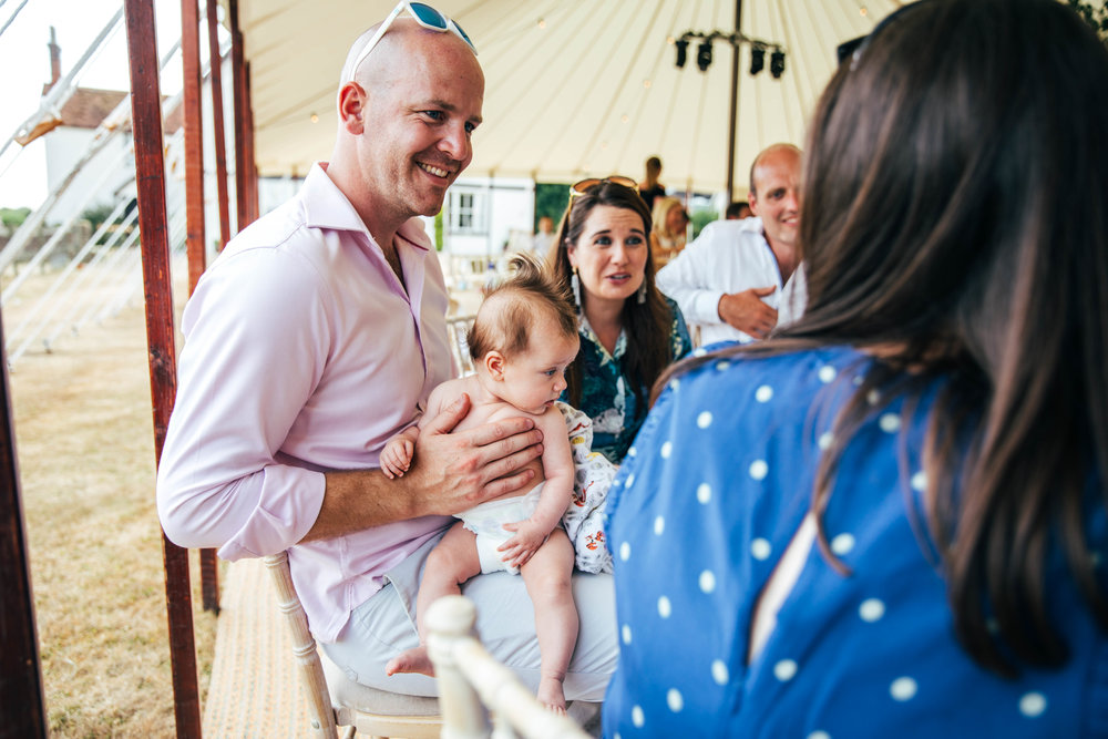 wedding guest holds baby on lap outdoor wedding. Essex Documentary Wedding Photographer