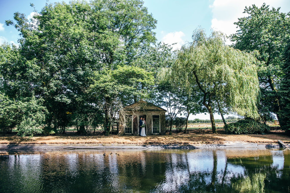 Bride and Groom by ruins over a lake, The long Barn.  Essex Documentary Wedding Photographer