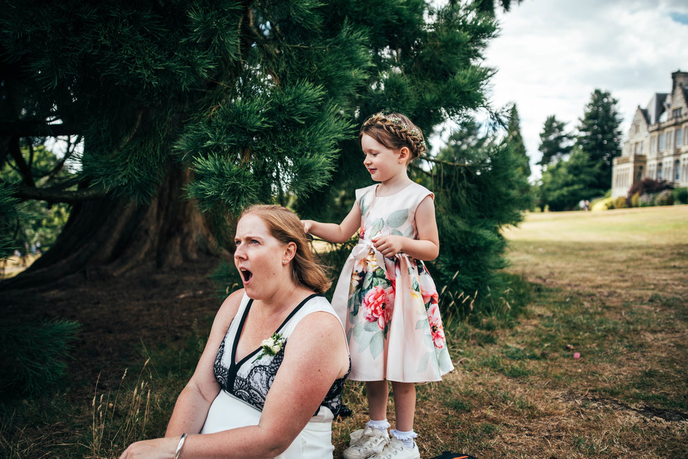 Flower girl brushes Mum's hair at Ashdown Park Hotel Wedding Essex Documentary Wedding Photographer