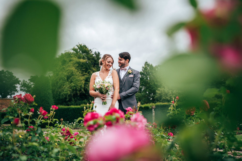 Bride and Groom in Rose Garden at Blake Hall, Ongar Essex Documentary Wedding Photographer