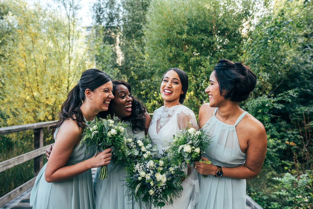 Bride and Bridesmaids laugh in grounds of Mile End Ecology Pavilion, Essex Documentary Wedding Photographer