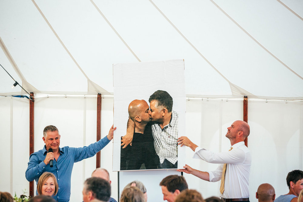 Best men hold up photo of Groom during speeches. Essex Documentary Wedding Photographer