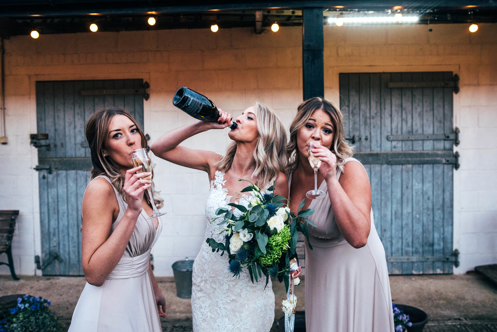 Bride drinks from champagne bottle Essex Documentary Wedding Photographer