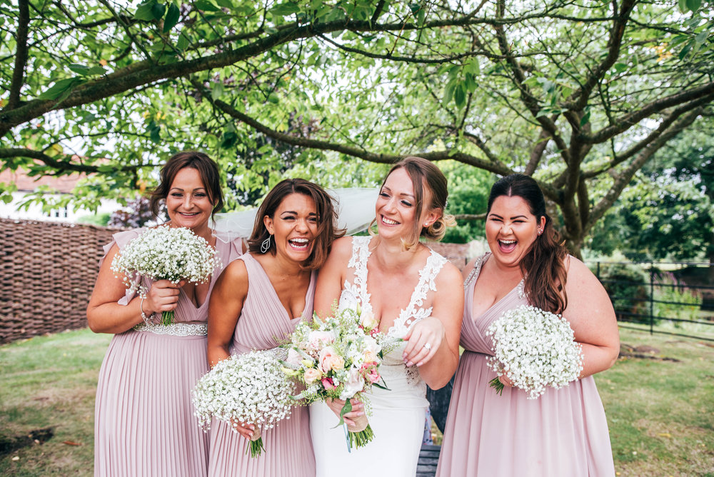Bride laughs with Bridesmaids in Pink for Blake Hall, Ongar Wedding Essex Documentary Wedding Photographer