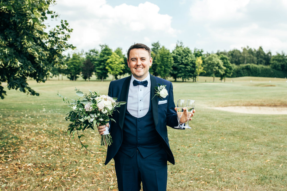 Best Man holds bottle and bouquet Stock Brook Manor, Billericay Essex Documentary Wedding Photographer