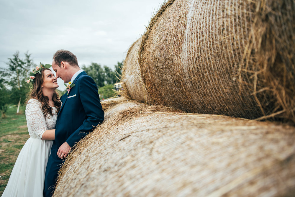 Boho Bride in Flower crown with Groom by Hay Bales in Bedinghams Farm, Ely Essex Documentary Wedding Photographer