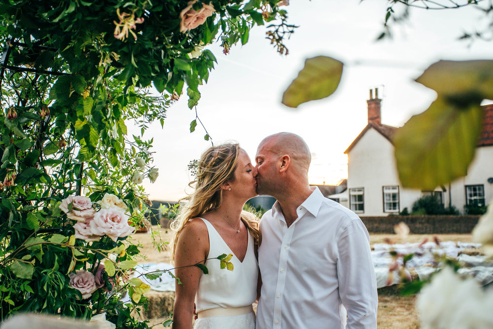 Bride and Groom kiss at Sunset under Flower Arch for outdoor, DIY Boho Wedding Essex Documentary Wedding Photographer