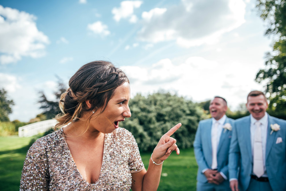 Bridesmaids tells off Groomsmen during group shots at Fennes Braintree, Essex Documentary Wedding Photographer
