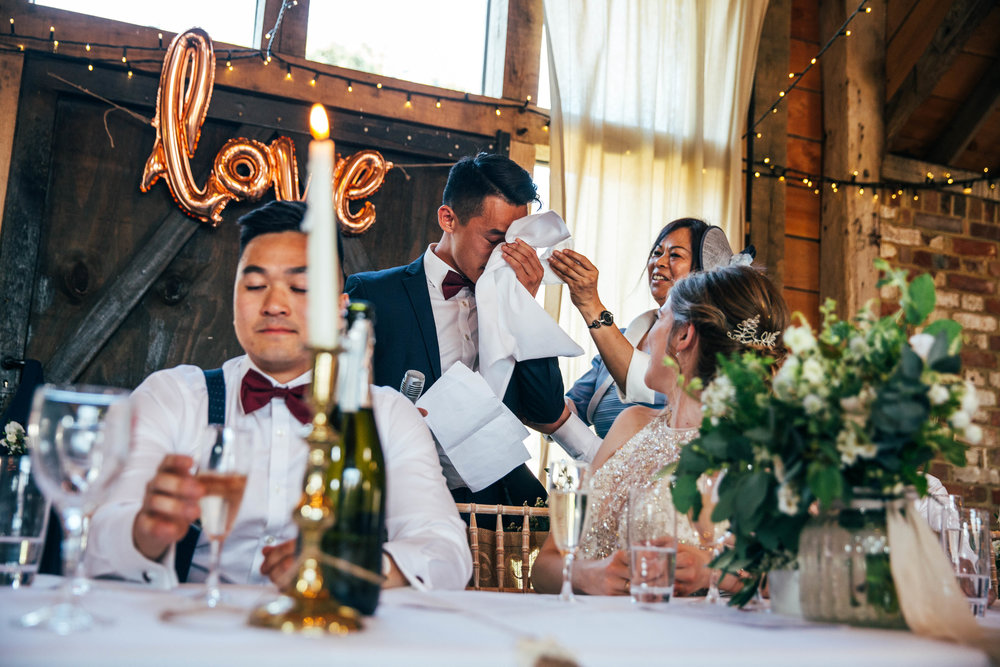 Grooms Mum wipes tear from Best Man during Speech at The Long Barn, Essex Documentary Wedding Photographer