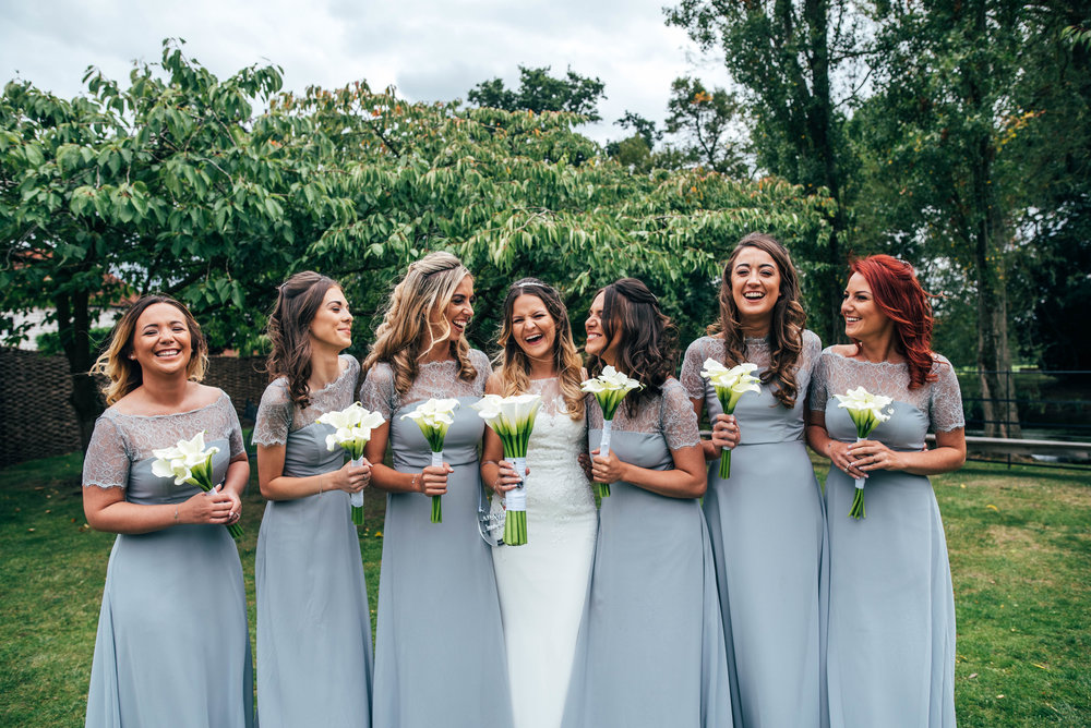 Bride and Bridesmaids in Blue laugh in gardens at Blake Hall, Ongar, Essex Documentary Wedding Photographer