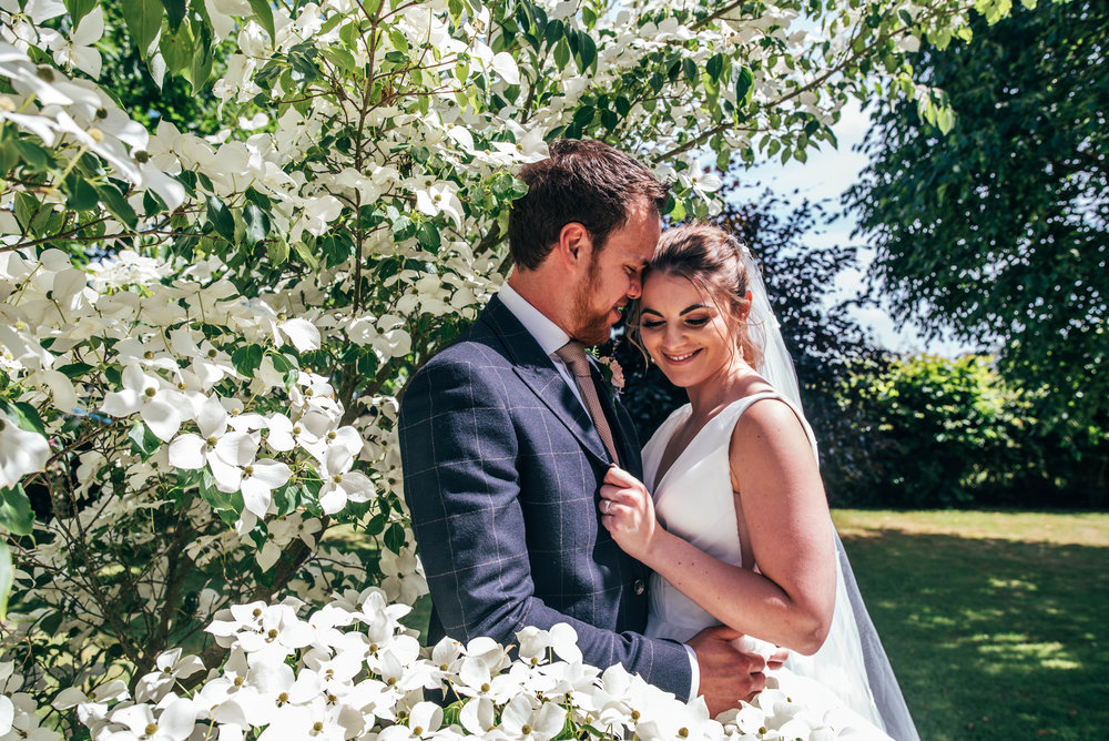 Bride and Groom by white flowered bush at Ratsbury Barn, Essex Documentary Wedding Photographer