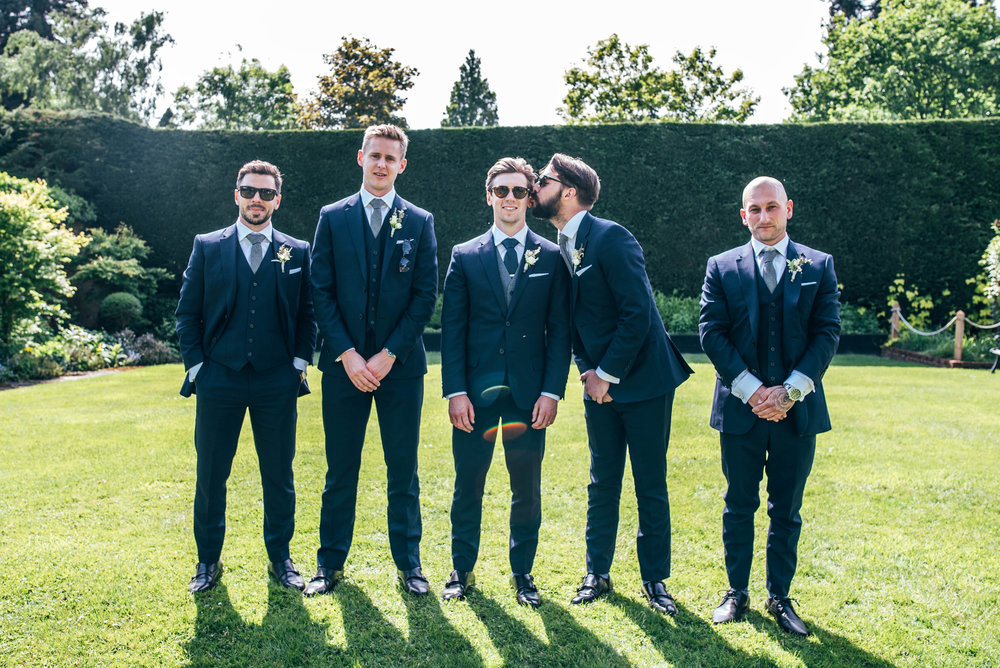 Best Man kisses Groom in group shot in gardens at Gaynes Park, Epping, Essex Documentary Wedding Photographer