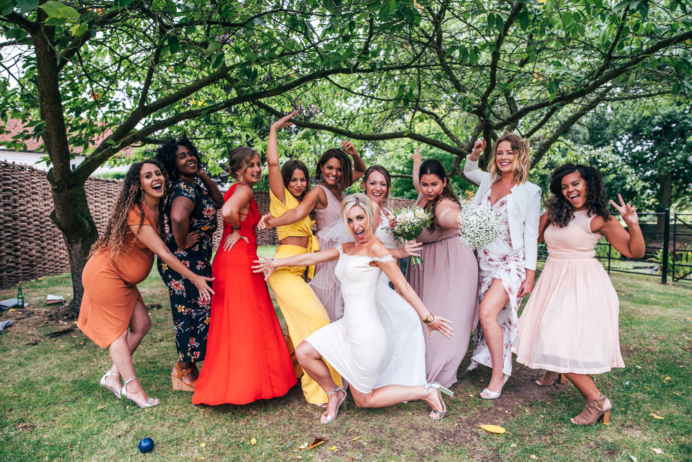 Bride with friends strike a pose in gardens at Blake Hall, Ongar, Essex Documentary Wedding Photographer