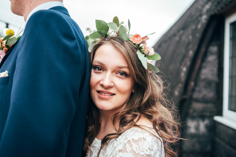 Boho Bride in Flower Crown looks at camera Bedinghams Farm, Ely, Essex Documentary Wedding Photographer