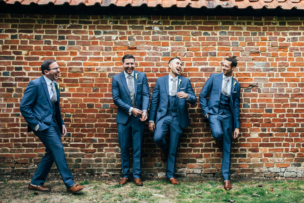 Groom and Groomsmen laugh against a wall at Blake Hall, Ongar, Essex Documentary Wedding Photographer