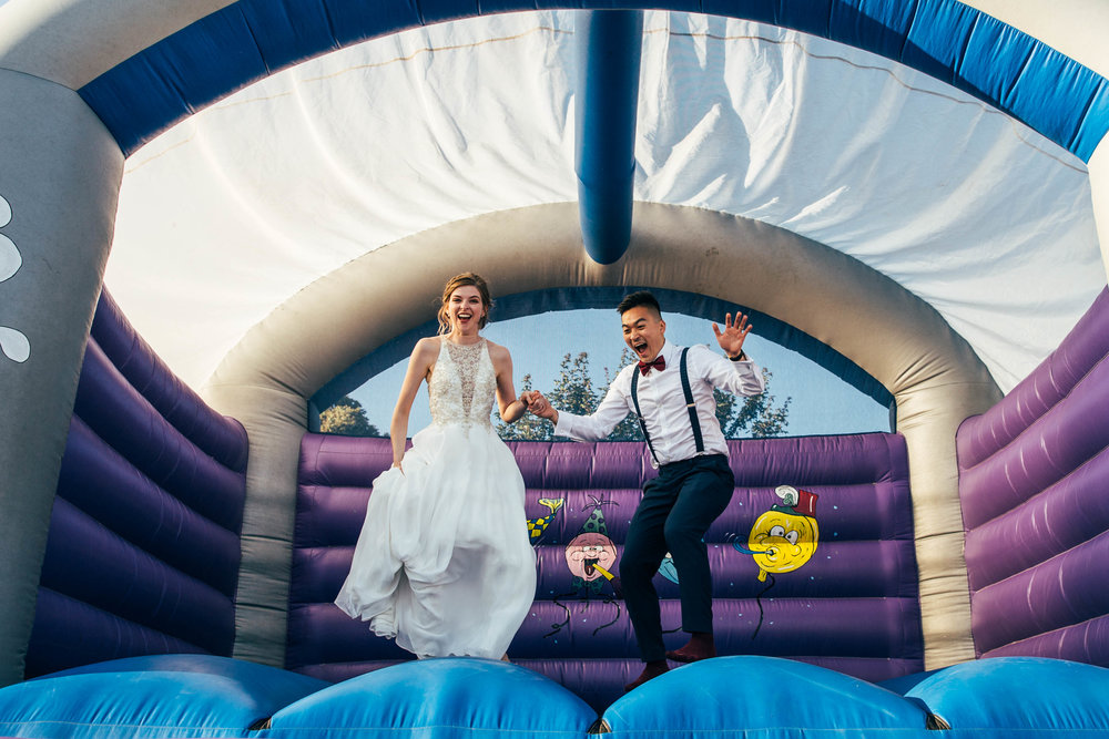 Bride and Groom jump on Bouncy Castle at The Long Barn, Essex Documentary Wedding Photographer