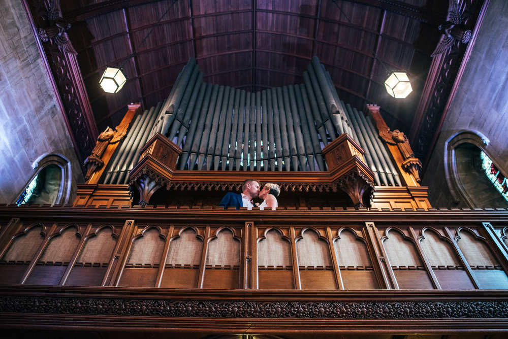 Bride and Groom on balcony in front of church organ at Ashdown Park Hotel, Essex Documentary Wedding Photographer
