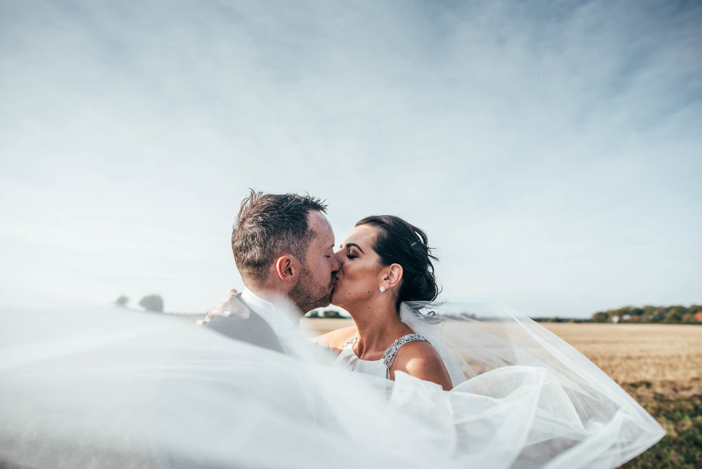 Bride and Groom kiss with windswept veil at The Compasses, Pattiswick, Essex Documentary Wedding Photographer