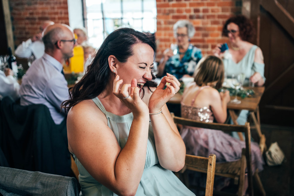 Bridesmaid pulls face after drinking a shot East Anglian Railway Museum Wedding Essex Documentary Wedding Photographer