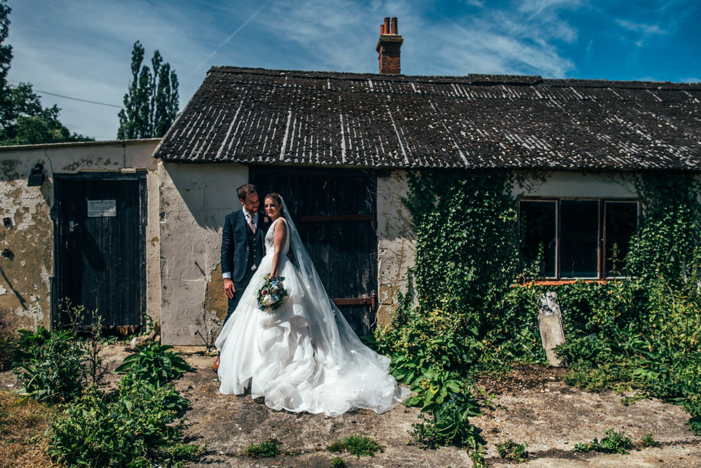Bride and Groom by derelict outbuilding at Ratsbury Barn, Essex Documentary Wedding Photographer