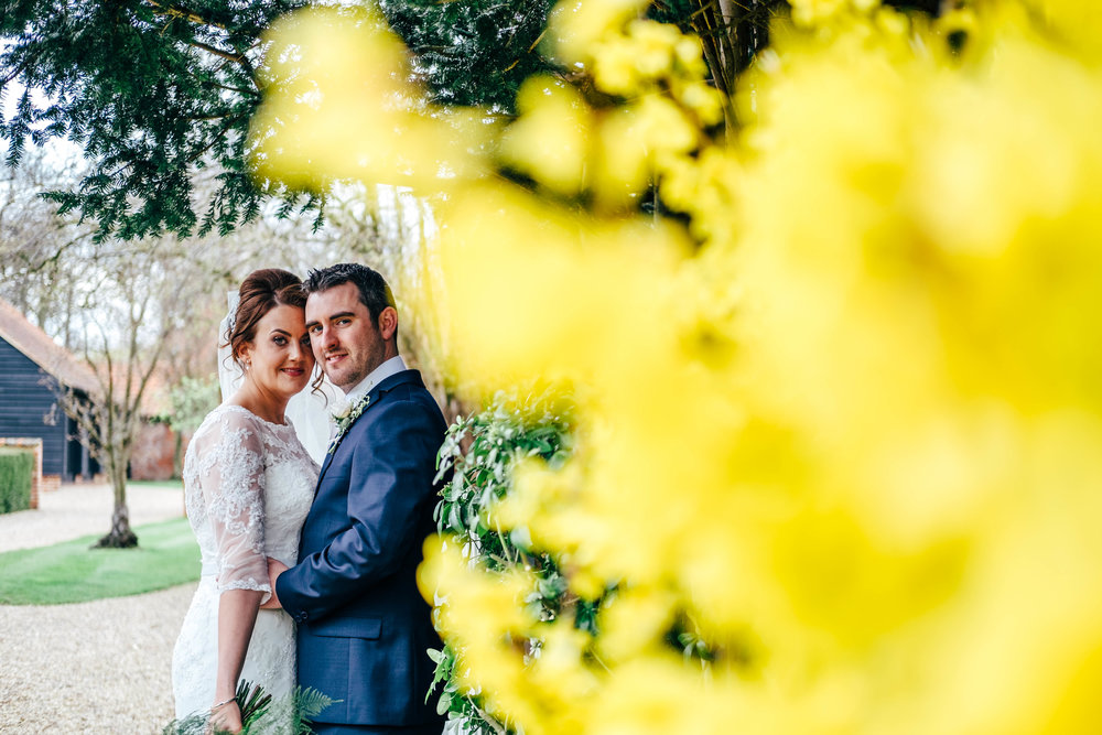 Bride & Groom by yellow flowers in gardens at Blake Hall, Ongar, Essex Documentary Wedding Photographer