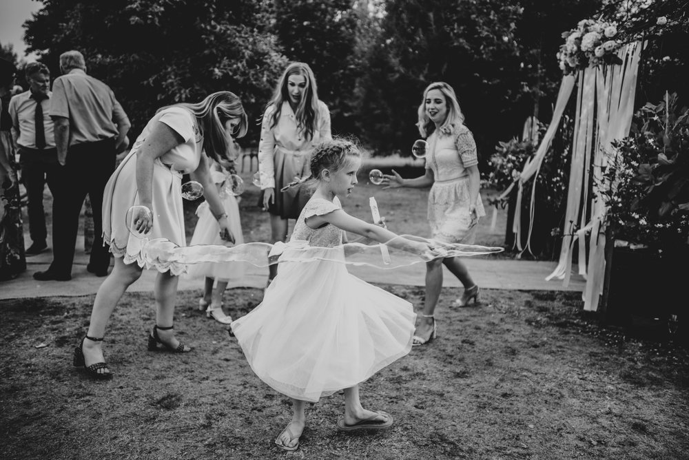 Flower girl waves bubble stick at laughing guests.  DIY Tipi wedding, Essex Documentary Wedding Photographer