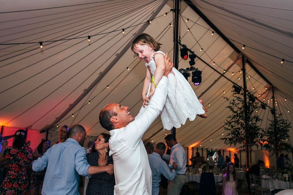 Wedding guest holds daughter in air on dance floor, DIY Wedding, Essex Documentary Wedding Photographer