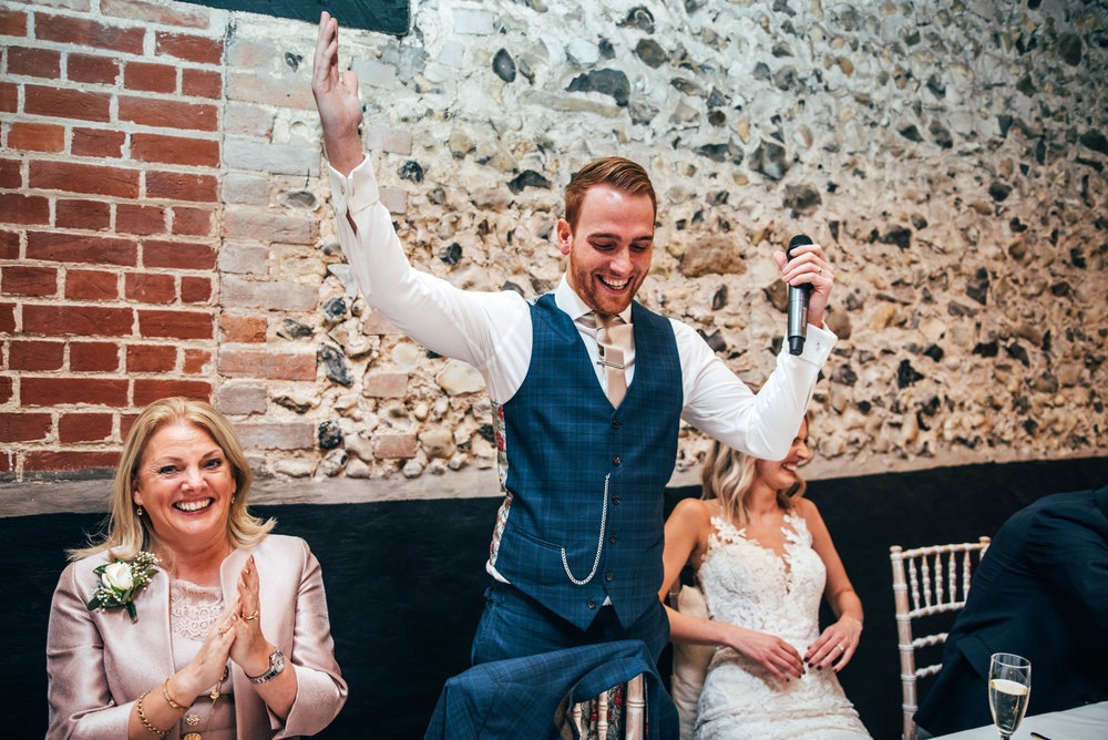 Groom raises arms in toast at The Granary Estates, Woodditton, Essex Documentary Wedding Photographer