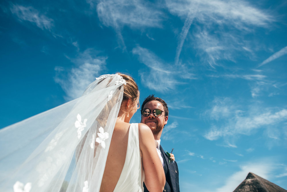 Brides reflection in Grooms glasses under blue skies at Ratsbury Barn, Essex Documentary Wedding Photographer