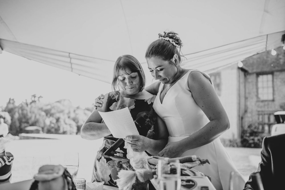 Bride helps emotional sister through her speech for Tipi Wedding at Ingatestone Hall, Essex Documentary Wedding Photographer