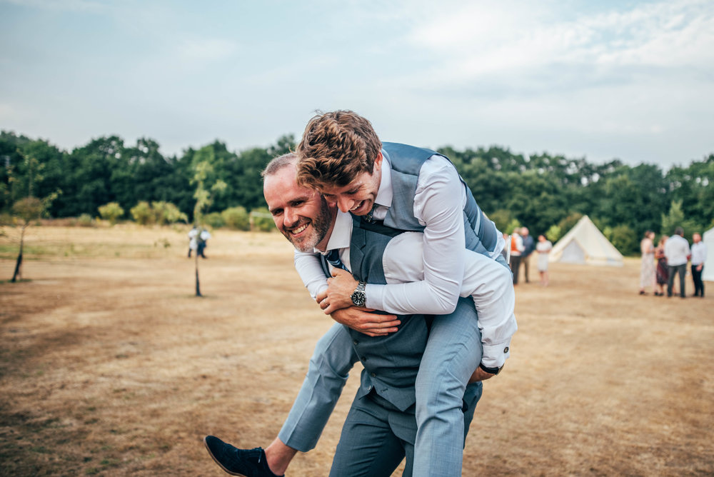 Wedding guest gives a piggy back, DIY Tipi wedding Essex Documentary Wedding Photographer