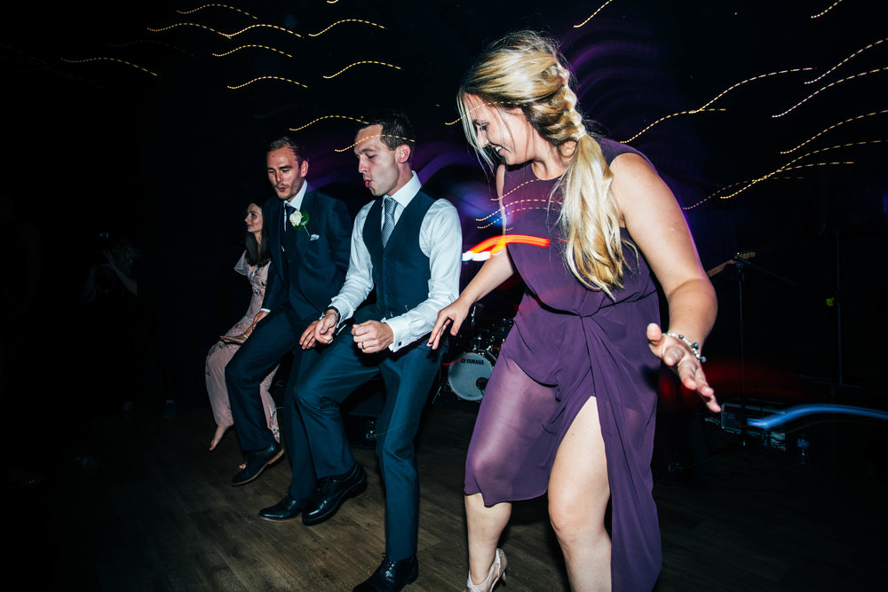 Groom with guests on dance floor at Hedingham Castle, Essex Documentary Wedding Photographer