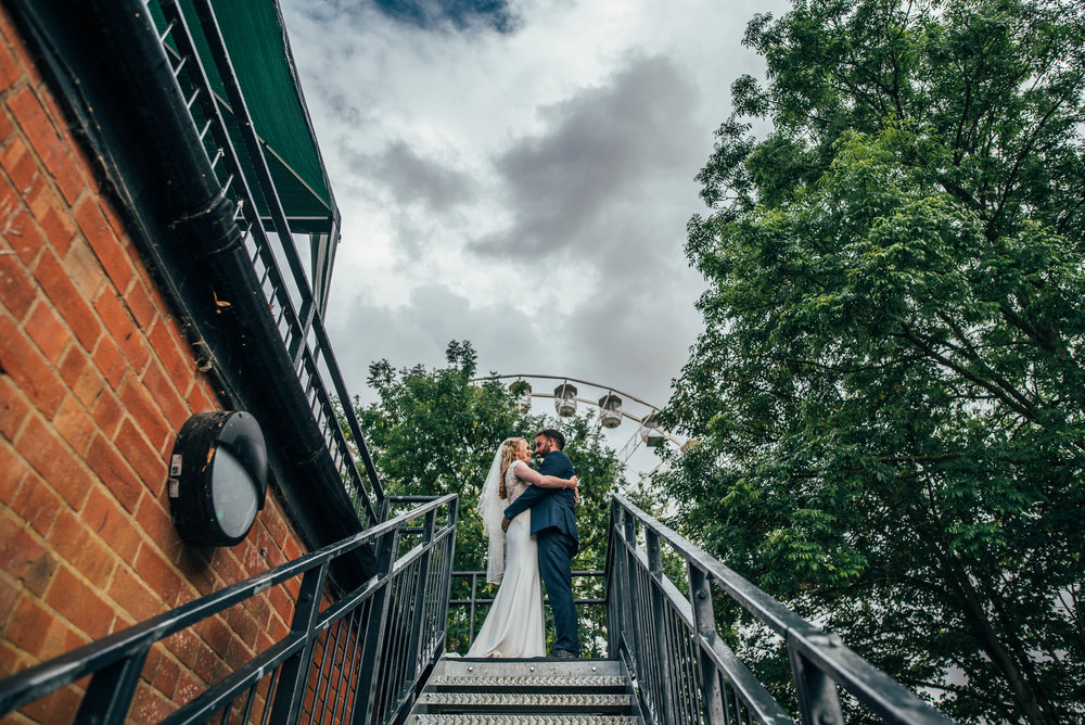 Bride and Groom at the top of iron stairs with Big Wheel behind them, Stratford Upon Avon Boat Club, Essex Documentary Wedding Photographer