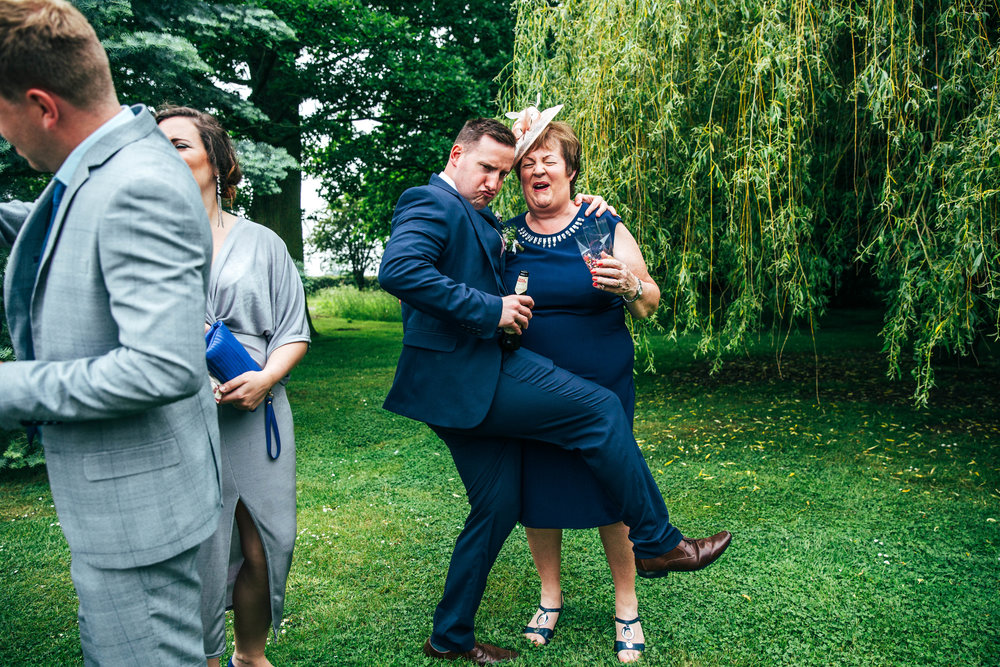 Wedding guest dances with Mother of the Groom in gardens at Blake Hall, Ongar, Essex Documentary Wedding Photographer
