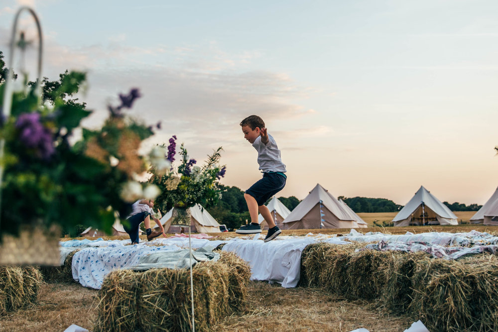 Little boy jumps over Hay Bale seats at sunset outdoor DIY wedding Essex Documentary Wedding Photographer