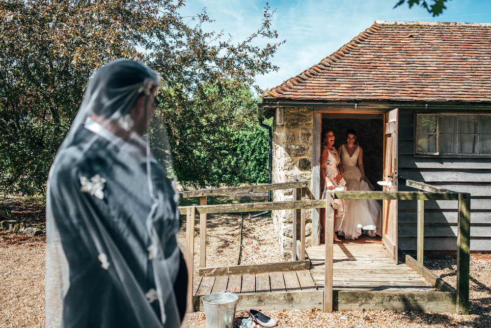 Bride and her mum laugh at Groom in veil, Ratsbury Barn, Essex Documentary Wedding Photographer