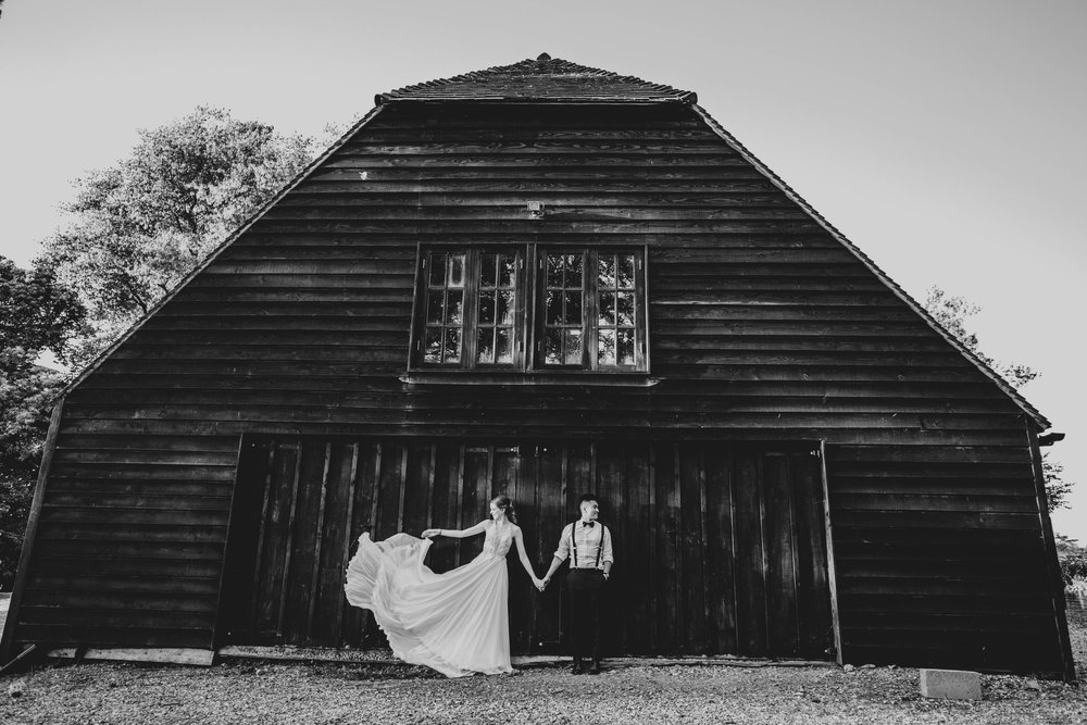 Bride with swish dress and Groom stand outside black barn at The Long Barn, Essex Documentary Wedding Photographer
