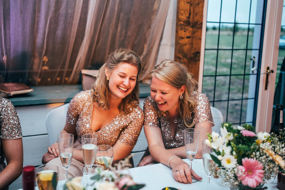 Bridesmaids laugh at speeches, Bedinghams Farm, Ely, Essex Documentary Wedding Photographer