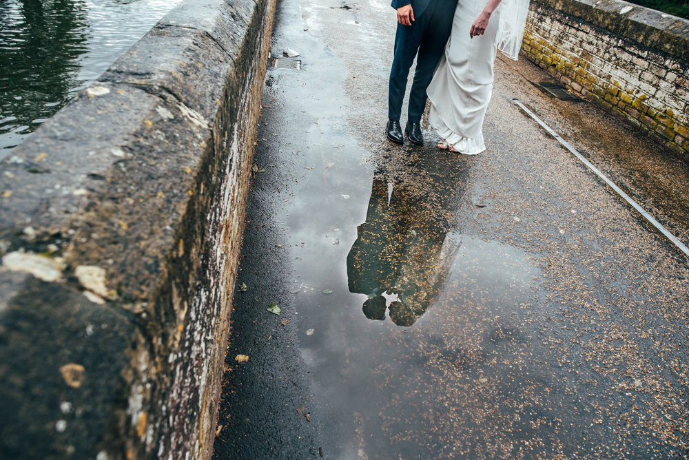 Bride and Groom reflection in puddle on rainy wedding, Essex Documentary Wedding Photographer