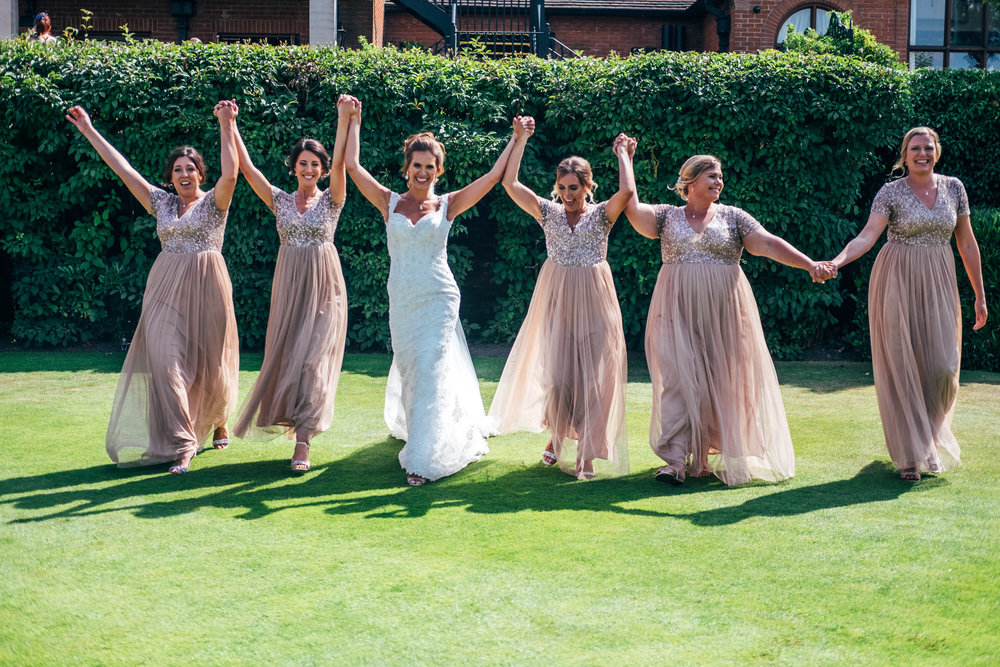 Bride and Bridesmaids cheer and raise arms on lawn at Stock Brook Manor, Billericay, Essex Documentary Wedding Photographer