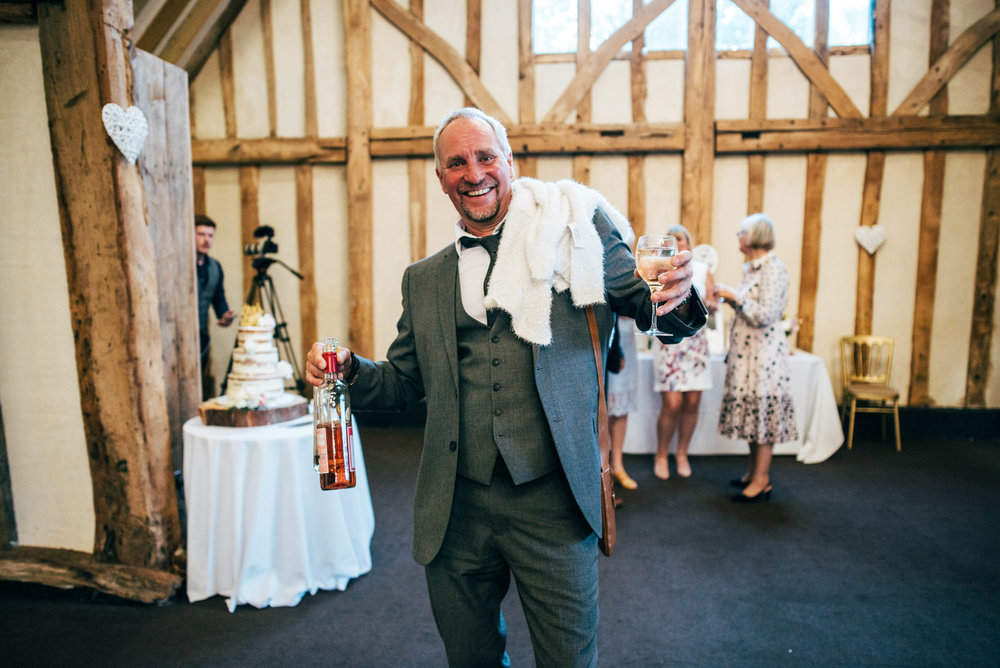 Wedding guest holds bottles at Blake Hall, Ongar, Essex Documentary Wedding Photographer