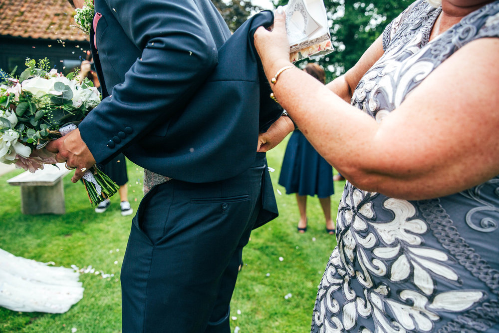 Mother of Groom puts confetti down Grooms trousers at Blake Hall, Ongar, Essex Documentary Wedding Photographer