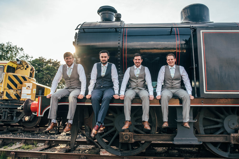 Groom and Groomsmen sit on train at East Anglian Railway Museum, Essex Documentary Wedding Photographer