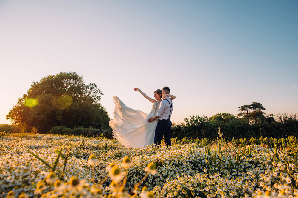 Bride wafts her dress in yellow field at sunset, The Long Barn, Essex Documentary Wedding Photographer