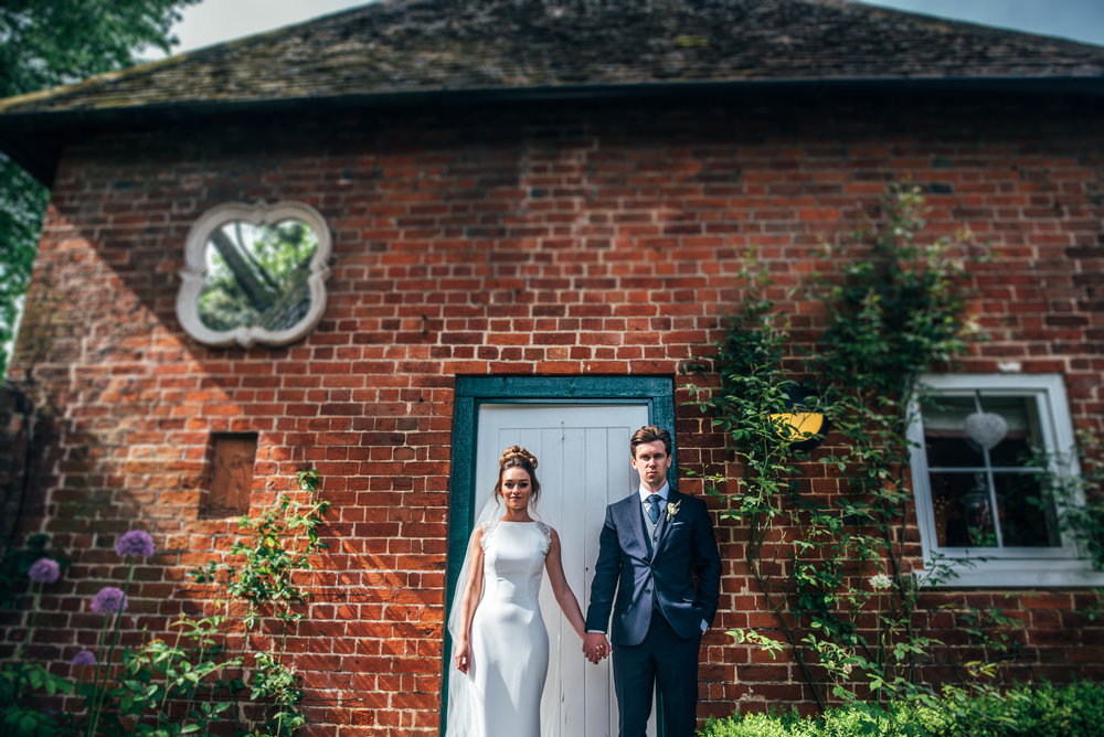 Bride and Groom hold hands outside cottage at Gaynes Park, Epping, Essex Documentary Wedding Photographer