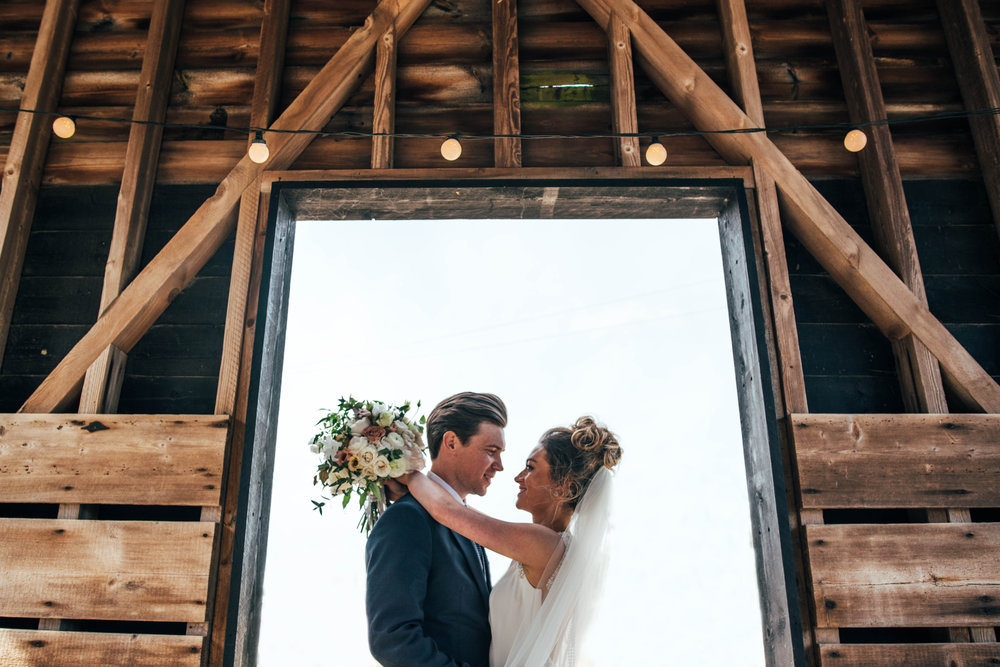Bride and Groom in barn doorway at Gaynes Park, Epping.  Essex Documentary Wedding Photographer