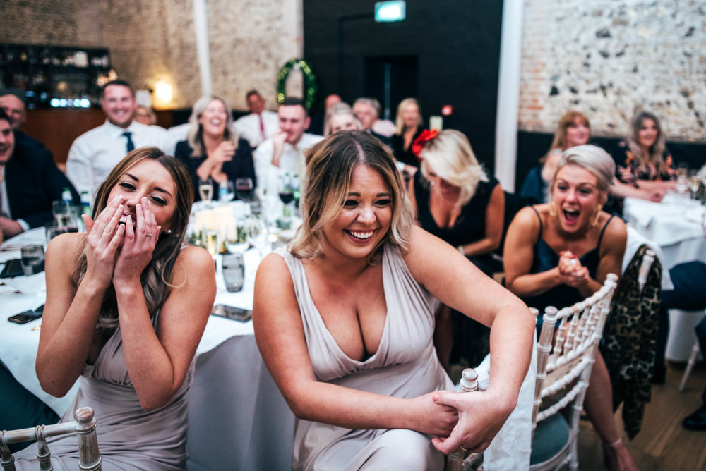 Bridesmaids laugh at speeches, The Granary Estates, Woodditton, Essex Documentary Wedding Photographer
