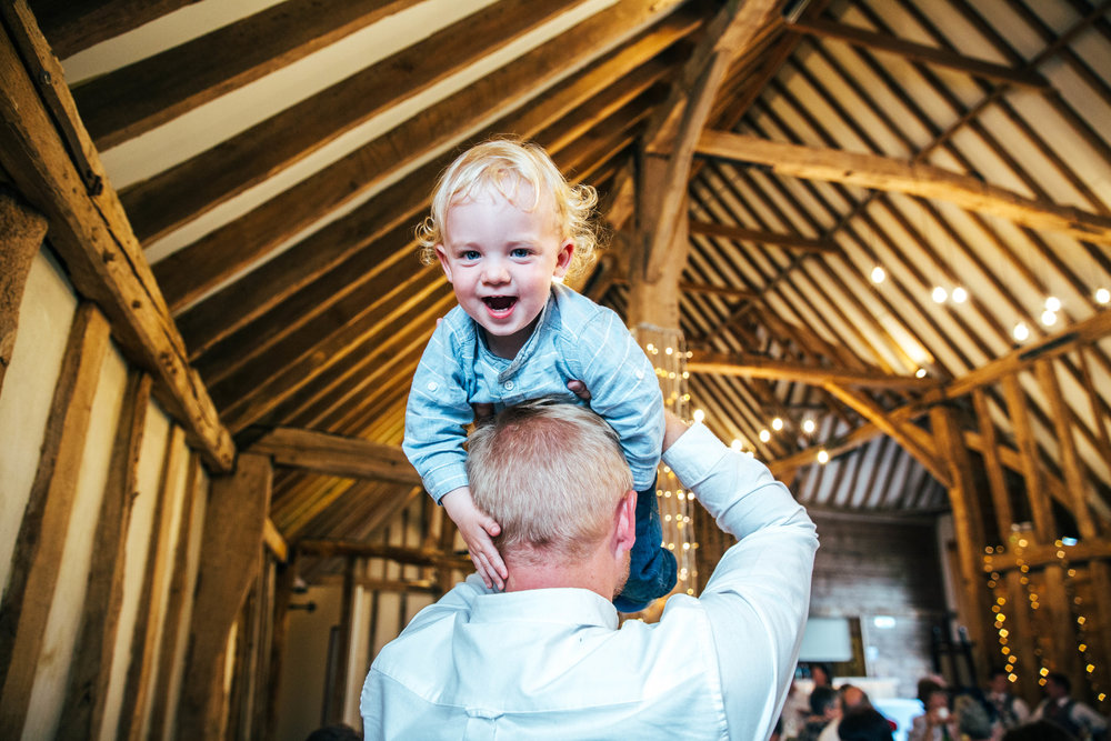 Guest holds toddler above head at Blake Hall, Ongar, Essex Documentary Wedding Photographer